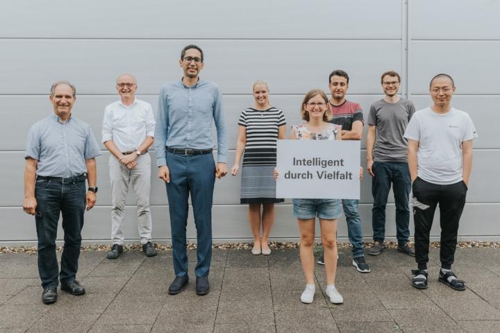 """Acht Menschen unterschiedlicher Herkunft, Größe, Geschlecht. In der Mitte wird ein Schild hochgehalten mit der Aufschrift """"Intelligent durch Vielfalt""""."""