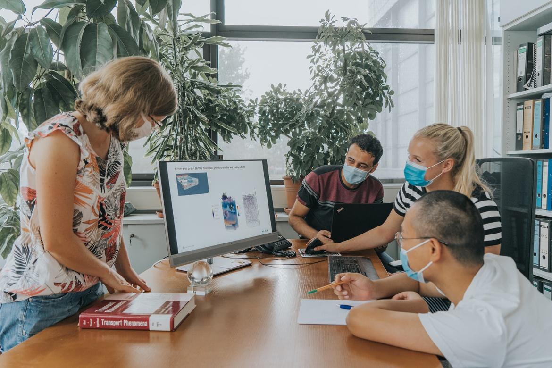 Zwei junge Frauen und zwei junge Männer schauen gemeinsam auf einen Computer-Bildschirm.