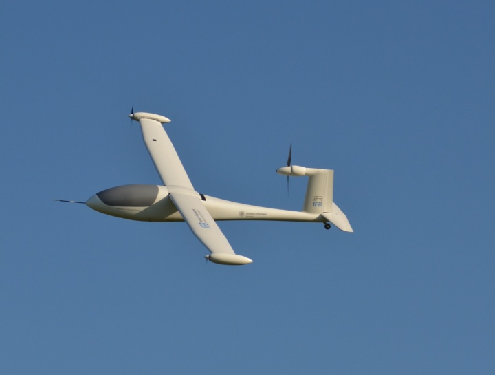 Das Flugzeugmodell mit dem Namen e-Genius Mod fliegt am blauen Himmel.