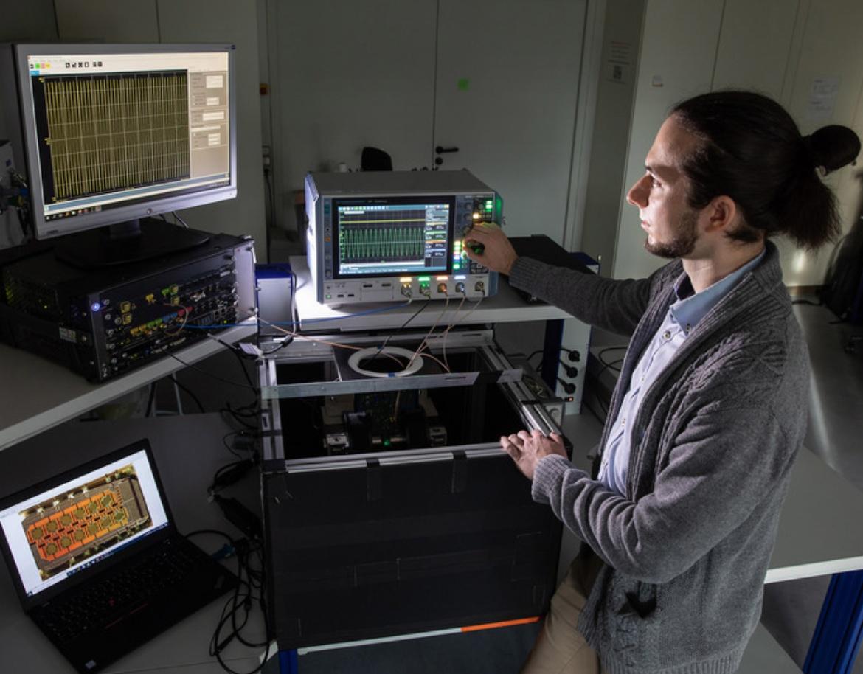 Ein Doktorand liest Messungen an mehreren Bildschrimen in einem Labor ab.