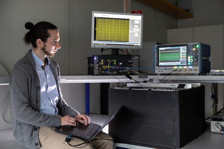 Ein Doktorand arbeitet mit einem Laptop an einem Messplatz in einem Labor.