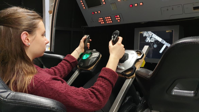 Eine Studentin liegt in einem Sitz im Sojus Simulator und steuert ihn mit Joysticks.
