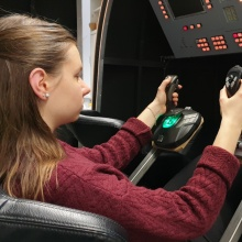 Student controls Soyuz simulator with joysticks.