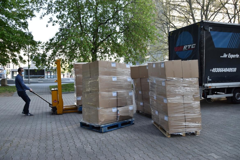 Ein Mitarbeiter lädt große Pakete mit Tests aus einem LKW aus.
