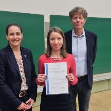 Die Gleichstellungsbeauftragte Prof. Nicole Radde (li.) und Prof. Jan Knippers übergeben Anna Schwarz eine Urkunde.