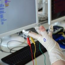 Verkabelte Hand, mit der ein Experiment durchgeführt wird.