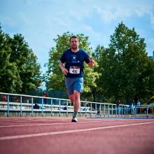 Sportler rennt auf einer Tartanbahn.