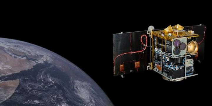 Eine Darstellung vom Kleinsatelliten Flying Laptop ohne Abdeckung im All, um die inneren Elemente zu zeigen. In Wirklichkeit ist der Satellit bedeckt.  (c) Jonas Keim, IRS, Universität Stuttgart. Darstellung mit Erde kreiert mit Canva.com