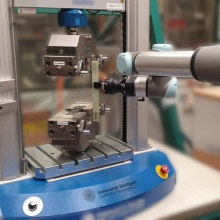 The collaborating robot inserts a material sample into the tensile tester.  Additional pieces of measuring equipment, such as e.g. cameras for carrying out the testing automatically, are integrated into the project.