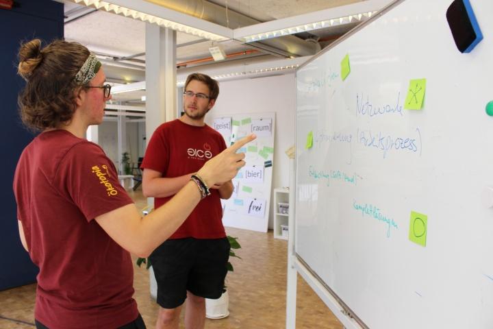 Studierende diskutieren im Gründer-Café an einem Whiteboard. (c) Universität Stuttgart