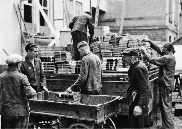 """Zwangsarbeiter aus der Sowjetunion verladen um 1944 die Bibliothek der Materialprüfungsanstalt. Der zweite Mann von links trägt auf der Jacke den Schriftzug """"OST"""", der ihn als """"Ostarbeiter"""" kenntlich macht."""