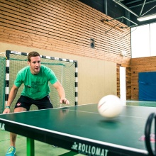 Student playing table tennis in a sports hall.