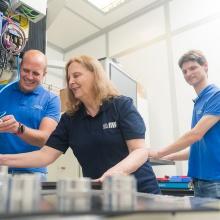 Zwei Wissenschaftler und eine Wissenschaftlerin arbeiten gemeinsam in einem Labor.