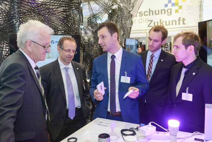 Ministerpräsident Winfried Kretschmann lässt sich von Prof. Albrecht Schmidt, Thomas Kubitza, Matthias Mögerle und Patrick Bader das Konzept ihres Startups meSchup zeigen.