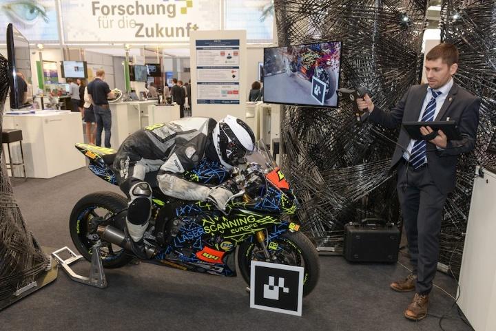 Thomas Obst, Forscher in der Abteilung Visualisierung am HLRS, erstellt einen 3D-Scan eines Motorrads. Der Bildschirm zeigt eine Strömungssimulation des gescannten Objekts.