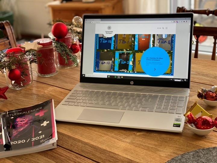 """The picture shows an open laptop and a book with the heading """"Study Planner"""" on a table. The screen shows the University of Stuttgart website. The table is decorated with Christmas decorations."""