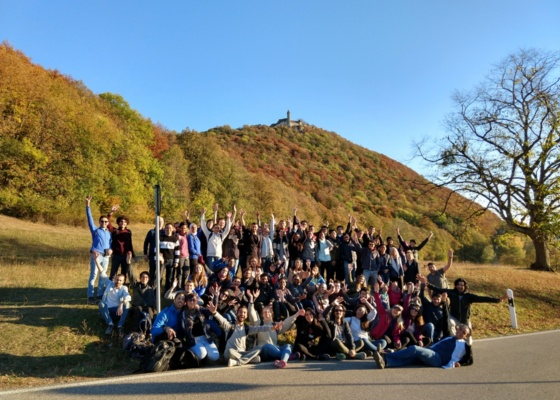 Viele Jugendliche sitzen am Fuße eines Bergs zu einer Burg