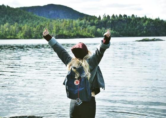 Junge Frau mit einem Rucksack steht vor einem See.