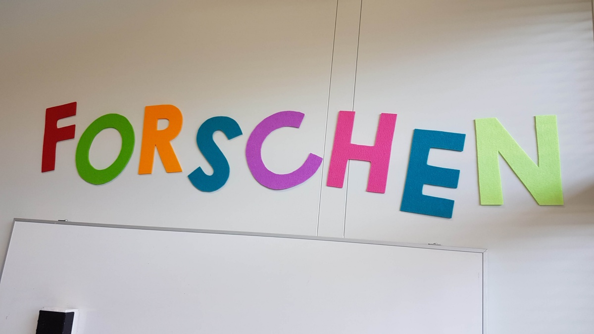Bunte Buchstaben an der Wand, die das Wort Forschen ergeben.