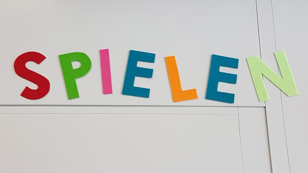 Bunte Buchstaben an der Wand, die das Wort Spielen ergeben.